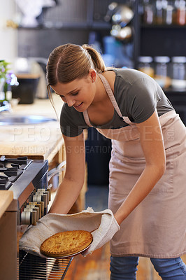 Buy stock photo Shot of an attractive young woman taking out a baked pie from the oven