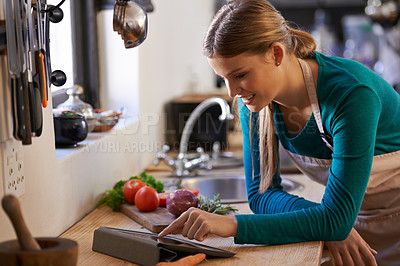 Buy stock photo Shot of a young woman looking at an online recipe on her digital tablet
