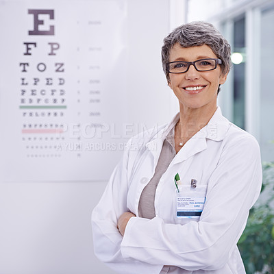 Buy stock photo Portrait of a female optometrist standing beside an eye test poster