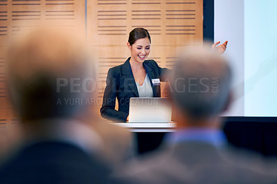 Buy stock photo A young businesswoman gesturing while giving a presentation at a press conference
