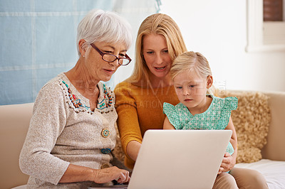 Buy stock photo Cropped shot of a young woman and her daughter sitting with a laptop indoors