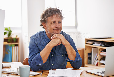 Buy stock photo Shot of a mature businessman looking thoughtful while sitting at his desk