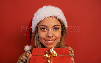Buy stock photo Shot of an attractive young woman wearing a Christmas hat on Christmas day