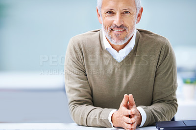 Buy stock photo Portrait of a mature businessman sitting at his office desk