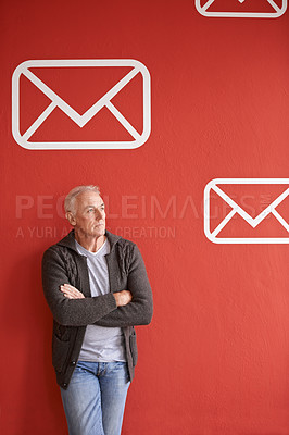 Buy stock photo Shot of a handsome senior man standing in front of a red background with a vector symbol for mail