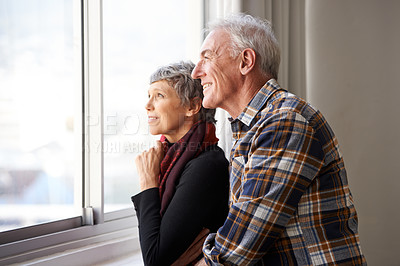 Buy stock photo Shot of a senior couple enjoying an affectionate moment by the window