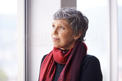 Buy stock photo Shot of a beautiful senior woman looking out of a window