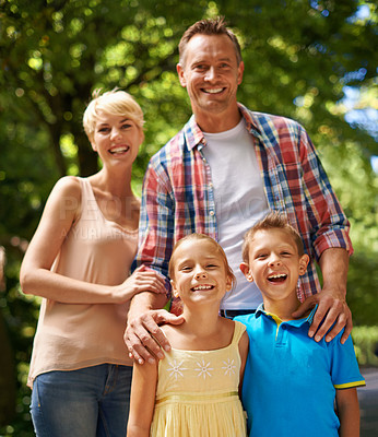 Buy stock photo A cropped portrait of a happy family standing together in a park on a sunny day