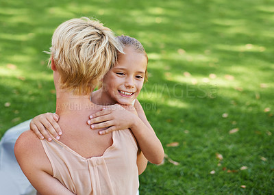 Buy stock photo A cropped shot of a little girl hugging her mom outdoors on a sunny day