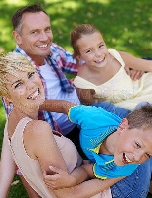 Buy stock photo A cropped portrait of a happy family sitting on the grass on a sunny day