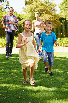 Buy stock photo A front view shot of a happy family playing in the park on a sunny day