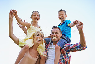 Buy stock photo A low angle portrait of two happy parents carrying their young children on their shoulders