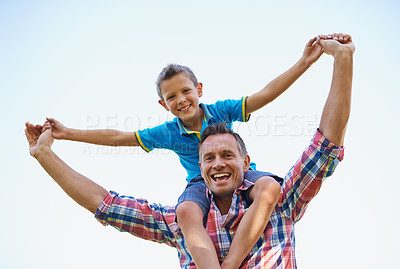 Buy stock photo A low angle portrait of a happy father carrying his young son on his shoulders