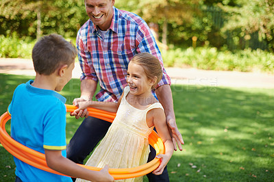 Buy stock photo A happy young family playing with hula hoops on a sunny day at the park
