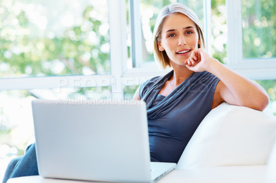 Buy stock photo View of woman sitting on sofa and working on laptop