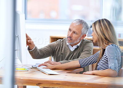 Buy stock photo Shot of a two coworkers having a discussion at a workstation