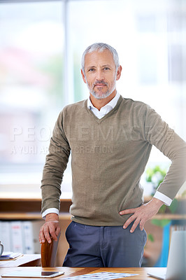 Buy stock photo A portrait of a confident businessman standing at his desk in the office
