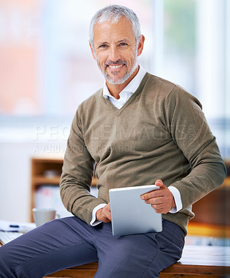 Buy stock photo A portrait of a happy businessman sitting on his desk with a tablet
