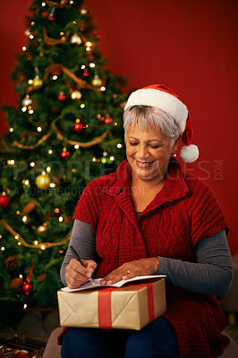 Buy stock photo Cropped shot of a mature woman writing a note at christmas