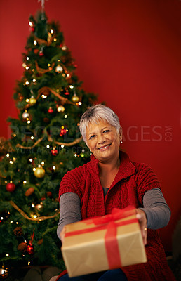 Buy stock photo Cropped shot of a mature woman offering a christmas present