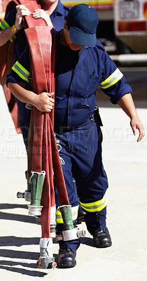 Buy stock photo Cropped shot of firemen carrying fire hoses
