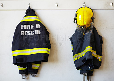 Buy stock photo Shot of firemen's clothing hanging from a wall