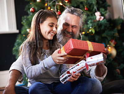 Buy stock photo Shot of a girl and her grandfather opening a gift together