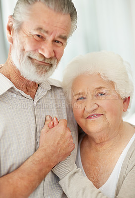 Buy stock photo Portrait of a smiling senior couple holding hands and smiling at the camera
