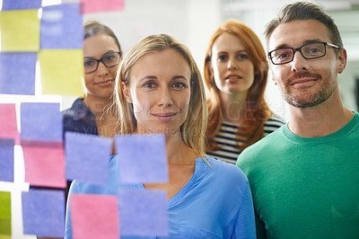 Buy stock photo Portrait of three business colleagues standing in front of a glass wall filled with sticky notes