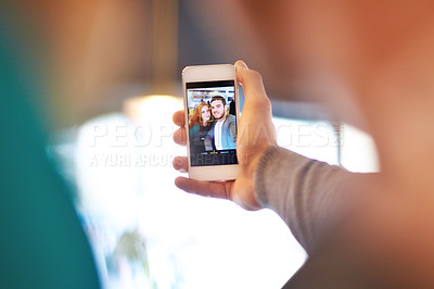 Buy stock photo Shot of a young couple taking a photo of themselves while on a date at a cafe
