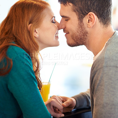 Buy stock photo Cropped shot of a happy young couple being affectionate while sitting at a cafe