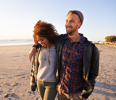 Buy stock photo Shot of a young couple enjoying a walk on the beach