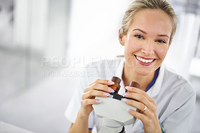 Buy stock photo Shot of a beautiful woman in a laboratory working with a microscope