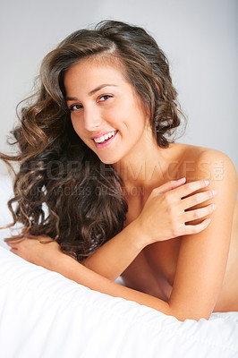 Buy stock photo Beautiful smiling brunette sitting on a bed covering her naked body in a white sheet