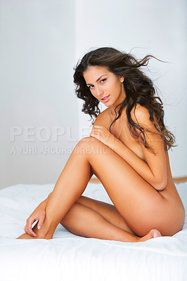 Buy stock photo Shot of a gorgeous young woman sitting naked on a bed