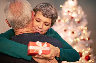 Buy stock photo Cropped shot of a happy mature couple embracing after exchanging Christmas gifts