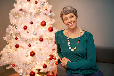 Buy stock photo A portrait of a happy mature woman sitting beside a white Christmas tree