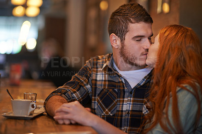 Buy stock photo Shot of an affectionate young couple sharing a kiss while on a coffee date