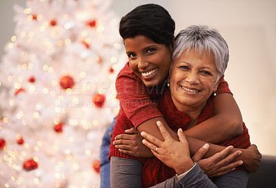 Buy stock photo A senior woman receiving a hug from her daughter on Christmas