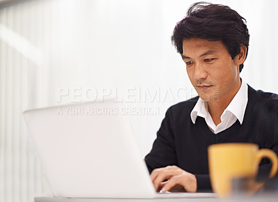 Buy stock photo Shot of a handsome asian businessman working on his laptop in the office