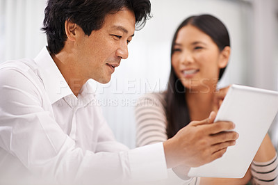 Buy stock photo Cropped shot of two asian business colleagues discussing work on a tablet