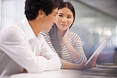 Buy stock photo Shot of two asian business colleagues sitting with a digital tablet and discussing work