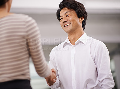 Buy stock photo Shot of two business partners shaking hands in an office setting
