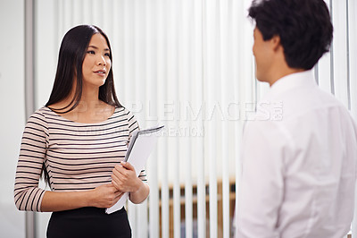 Buy stock photo Shot of a young asian businesswoman speaking to a colleague in the office