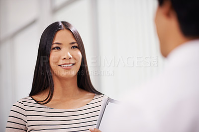 Buy stock photo Shot of a young asian office worker speaking to a colleague