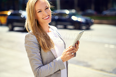 Buy stock photo A young businesswoman using her tablet in the city