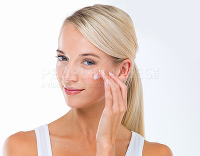 Buy stock photo A beautiful young woman applying moisturizer to her face