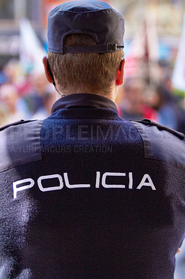 """Buy stock photo Rearview shot of a policeman wearing a uniform with the word, """"POLICIA"""" on the back"""