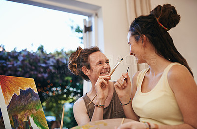 Buy stock photo A young couple painting together and having fun