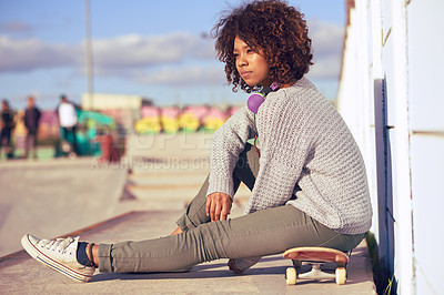 Buy stock photo Shot of a young woman out skateboarding in the city